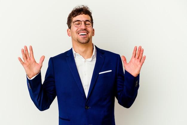 白い背景に孤立した若いビジネス白人男性は、胸に手を置いて大声で笑います。