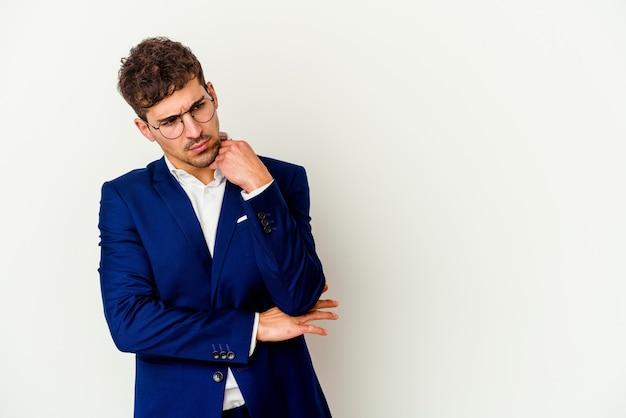 Молодой деловой человек кавказской изолирован на белом фоне, глядя в сторону с сомнительным и скептическим выражением лица.