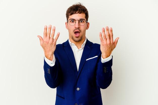 젊은 비즈니스 백인 남자 손으로 번호 10을 보여주는 흰색 배경에 고립.