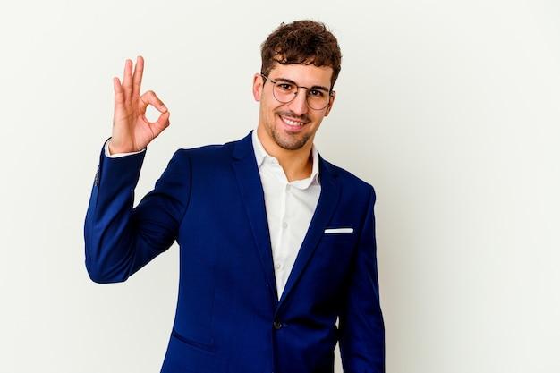 Молодой деловой кавказец, изолированный на белом, подмигивает и держит рукой жест.