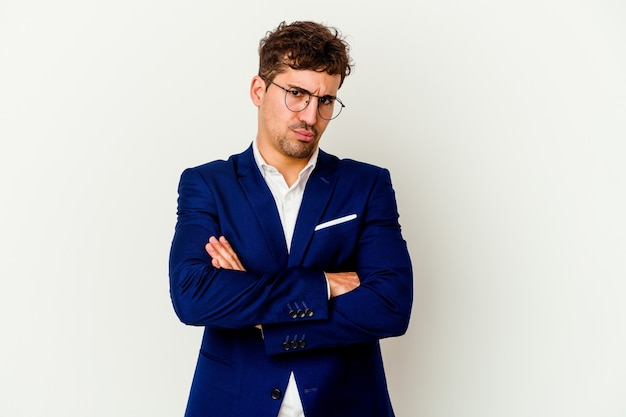 Young business caucasian man isolated on white background frowning face in displeasure, keeps arms folded.