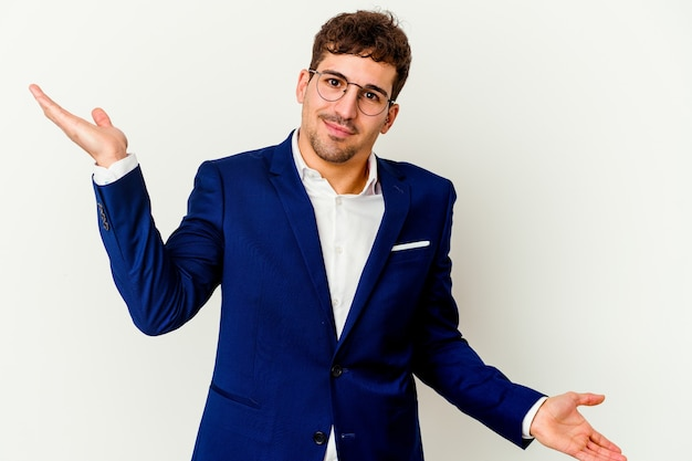 Young business caucasian man isolated on white background makes scale with arms, feels happy and confident.