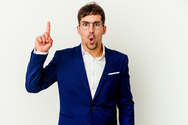 Young business caucasian man isolated on white background pointing upside with opened mouth.