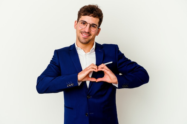 Young business caucasian man isolated on white wall smiling and showing a heart shape with hands.