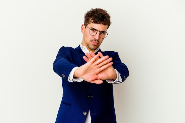 Young business caucasian man isolated on white wall standing with outstretched hand showing stop sign, preventing you.