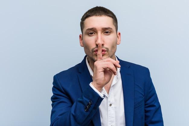 Молодой деловой человек кавказской хранит в секрете или просит молчания.