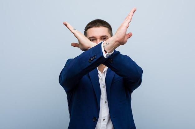 Молодой деловой человек кавказской держит скрещенными руками, концепцию отрицания.
