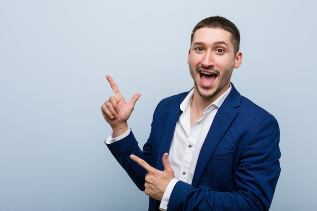 Young business caucasian man pointing with forefingers to a copy , expressing excitement and desire.