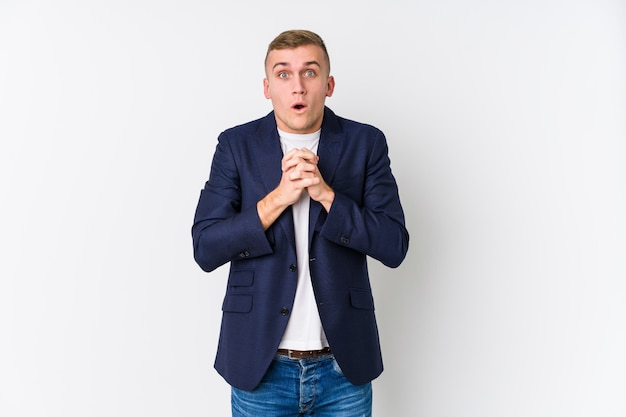 Young business caucasian man praying for luck, amazed and opening mouth looking to front.