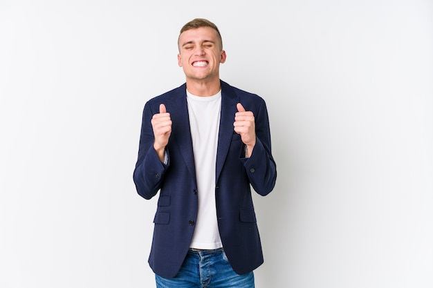 Young business caucasian man raising fist, feeling happy and successful. victory concept.