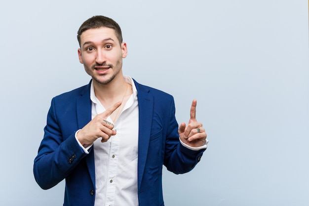 Young business caucasian man shocked pointing with index fingers to a copy space.