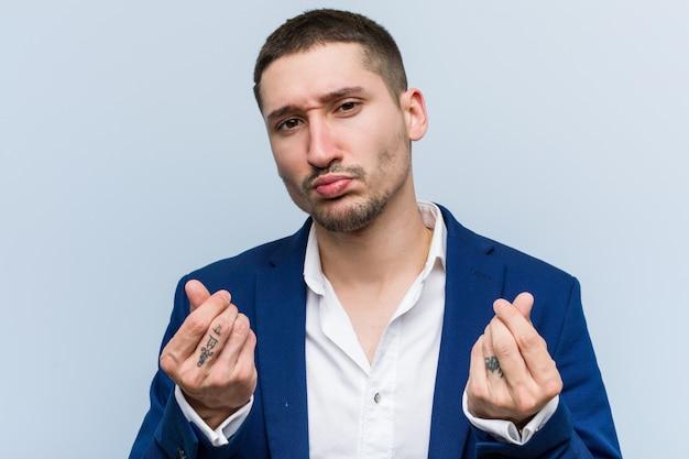 Young business caucasian man showing that he has no money.