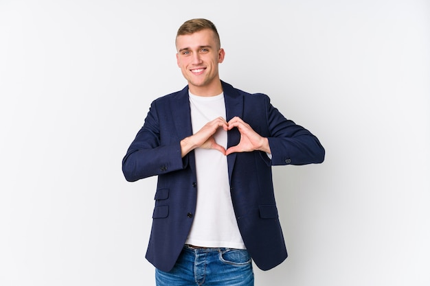 Young business caucasian man smiling and showing a heart shape with hands.