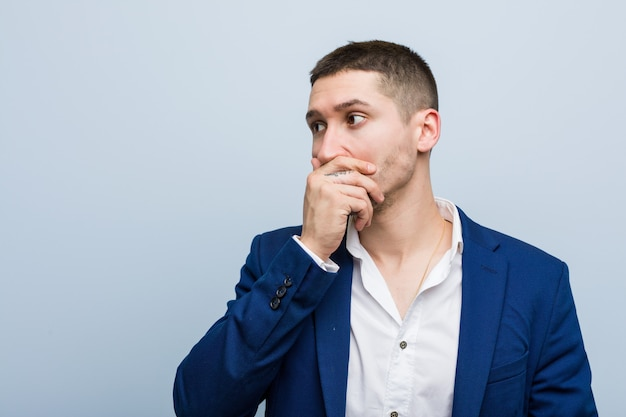 Young business caucasian man thoughtful looking to a copy space covering mouth with hand.