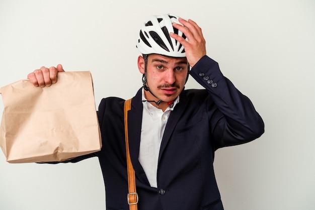 自転車のヘルメットをかぶり、白い背景に食べ物を持ち歩く若いビジネス白人男性がショックを受け、彼女は重要な会議を思い出しました。