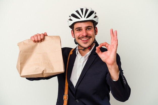 自転車のヘルメットを着用し、白い背景に分離されたテイク ウェイ フードを保持している若いビジネス白人男性は、陽気で自信を持って ok のジェスチャーを示しています。
