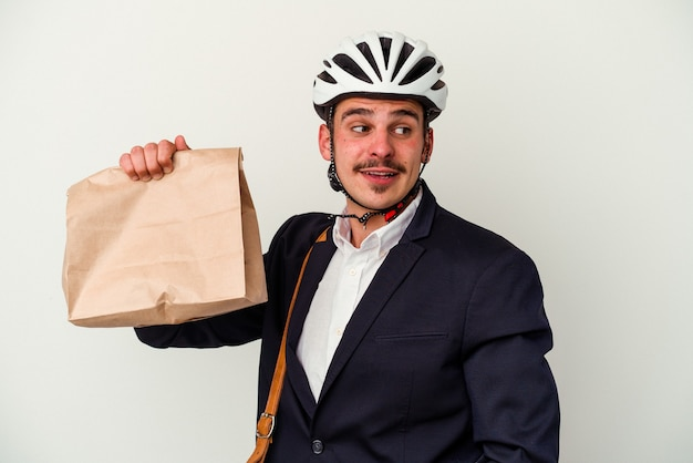 自転車のヘルメットをかぶり、白い背景に隔離された食べ物を持っている若いビジネス白人男性は、笑顔で陽気で快適に見えます。