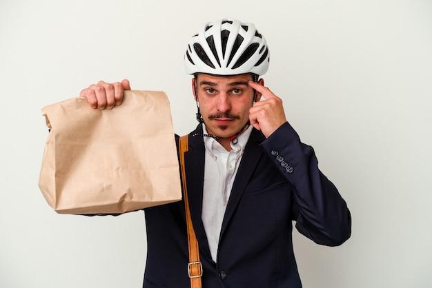 自転車のヘルメットをかぶり、白い背景に食べ物を持ち、指で寺院を指し、考え、仕事に集中した若いビジネス白人男性。