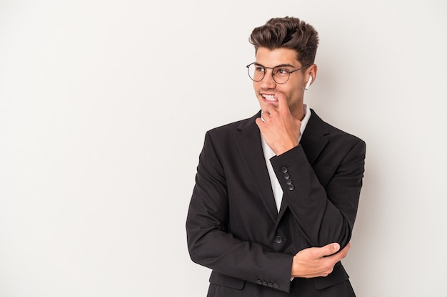 白い背景で隔離のヘッドフォンを身に着けている若いビジネス白人男性は、コピースペースを見ている何かについて考えてリラックスしました。