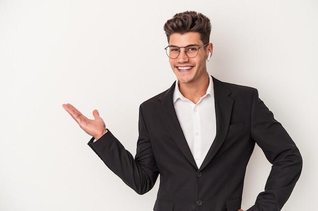手のひらにコピースペースを示し、腰に別の手を保持している白い背景で隔離のヘッドフォンを身に着けている若いビジネス白人男性。