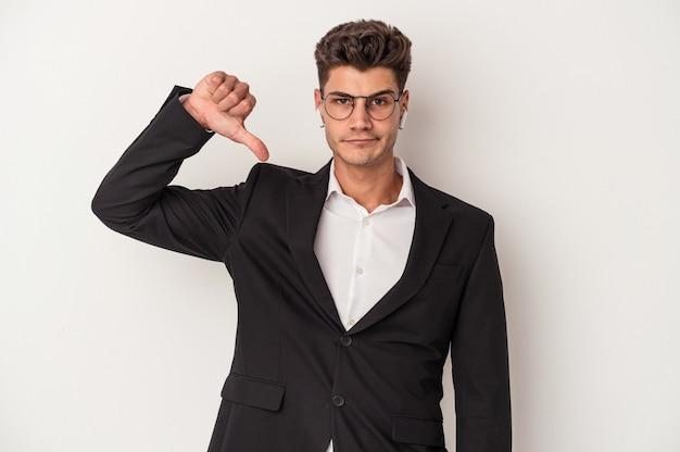 嫌いなジェスチャーを示す白い背景に分離されたヘッドフォンを身に着けている若いビジネス白人男性は、親指を下に向けます。不一致の概念。