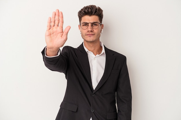 白い背景に分離されたヘッドフォンを身に着けている若いビジネス白人男性は、一時停止の標識を示している手を伸ばして立って、あなたを防ぎます。