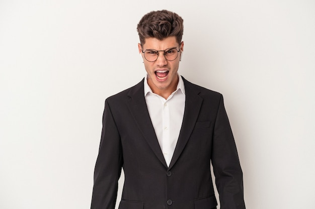 Young business caucasian man wearing headphones isolated on white background screaming very angry and aggressive.