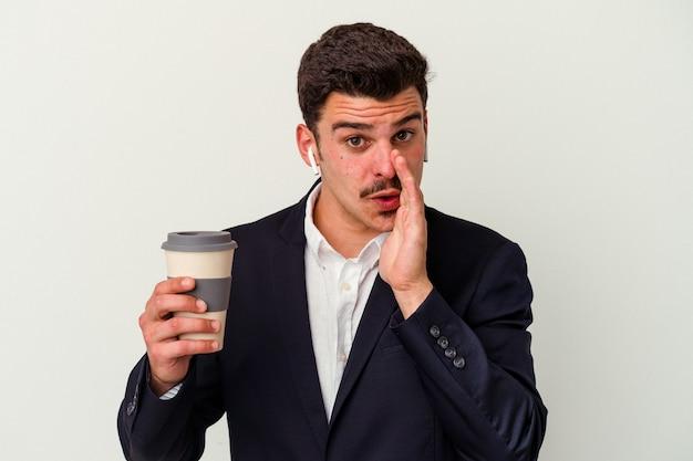 ワイヤレス ヘッドフォンを着用し、白い背景に隔離されたテイク ウェイ コーヒーを保持している若いビジネス白人男性が秘密の熱いブレーキ ニュースを言って、よそ見