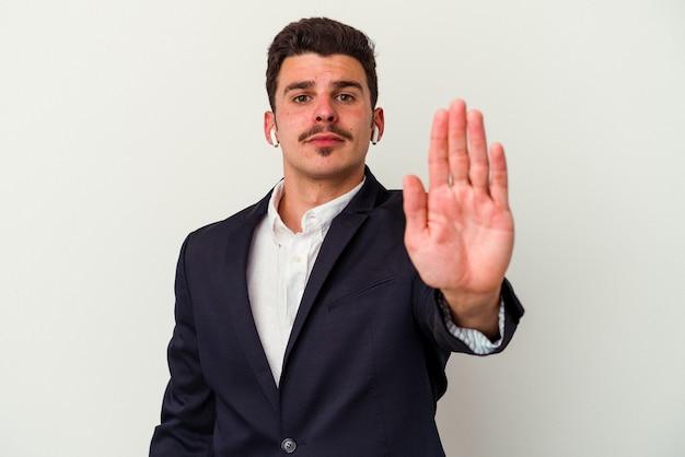 一時停止の標識を示す差し出された手で立っている白い背景に分離されたワイヤレス ヘッドフォンを身に着けている若いビジネス白人男性は、あなたを防ぎます。