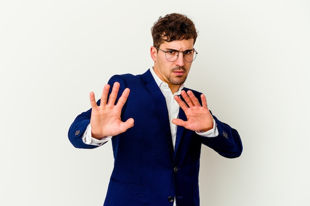 Young business caucasian man on white rejecting someone showing a gesture of disgust.