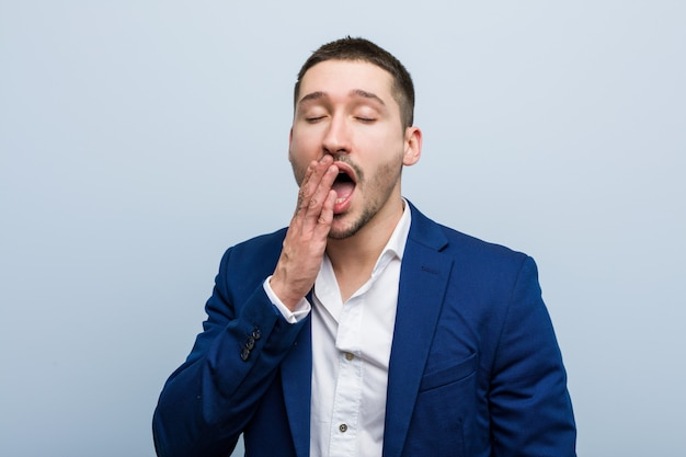 Young business caucasian man yawning showing a tired gesture covering mouth with him hand.