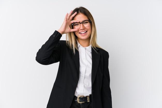 若いビジネス白人女性は目にokのしぐさを維持して興奮しています。