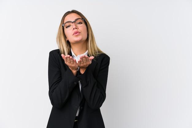 若いビジネス白人女性の唇を折りたたみ、空気キスを送信するために手のひらを保持しています。