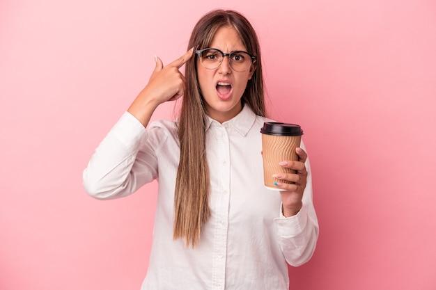 人差し指で失望のジェスチャーを示すピンクの背景に孤立したテイクアウトを保持している若いビジネス白人女性。