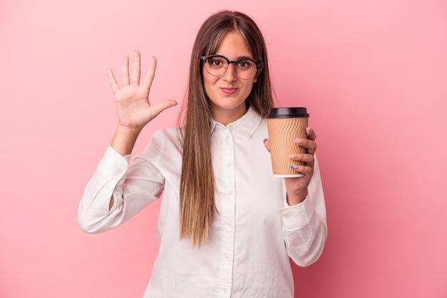 ピンクの背景に孤立したテイクアウトを保持している若いビジネス白人女性は、指で5番目を示す陽気な笑顔を浮かべています。