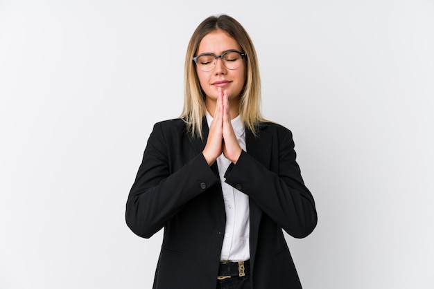 Young business caucasian woman holding hands in pray near mouth, feels confident.