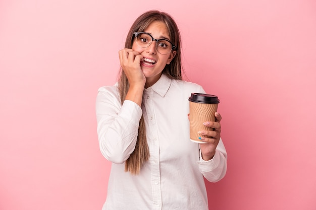Young business caucasian woman holding a take away isolated on pink background biting fingernails, nervous and very anxious.