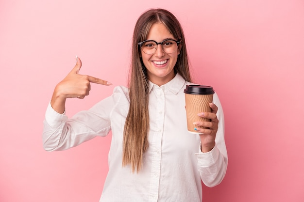Young business caucasian woman holding a take away isolated on pink background person pointing by hand to a shirt copy space, proud and confident
