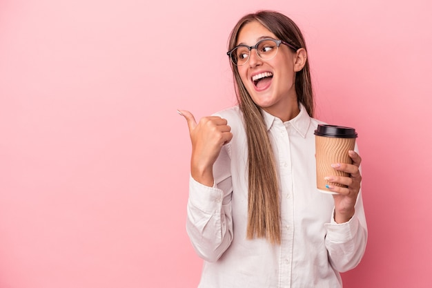 Young business caucasian woman holding a take away isolated on pink background points with thumb finger away, laughing and carefree.