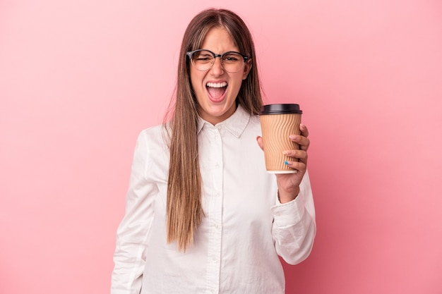 Young business caucasian woman holding a take away isolated on pink background screaming very angry and aggressive.