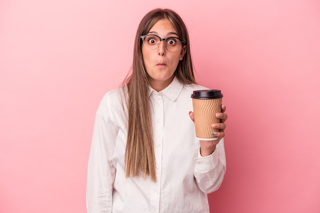 Young business caucasian woman holding a take away isolated on pink background shrugs shoulders and open eyes confused.