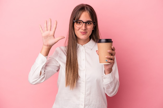 Young business caucasian woman holding a take away isolated on pink background smiling cheerful showing number five with fingers.