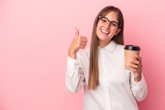 Young business caucasian woman holding a take away isolated on pink background smiling and raising thumb up