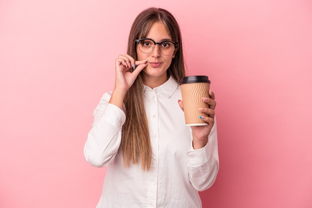 Young business caucasian woman holding a take away isolated on pink background with fingers on lips keeping a secret.