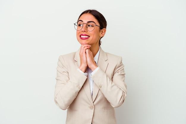 흰색 배경에 고립 된 젊은 비즈니스 백인 여자 손을 턱 아래 유지, 행복 하 게 옆으로 찾고 있습니다.