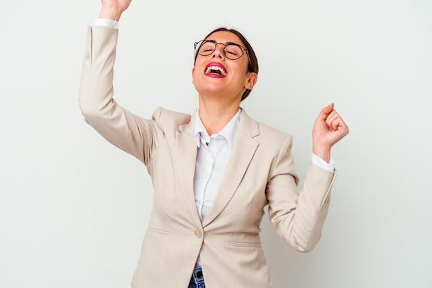 特別な日を祝って白で孤立した若いビジネス白人女性は、エネルギーでジャンプして腕を上げます。