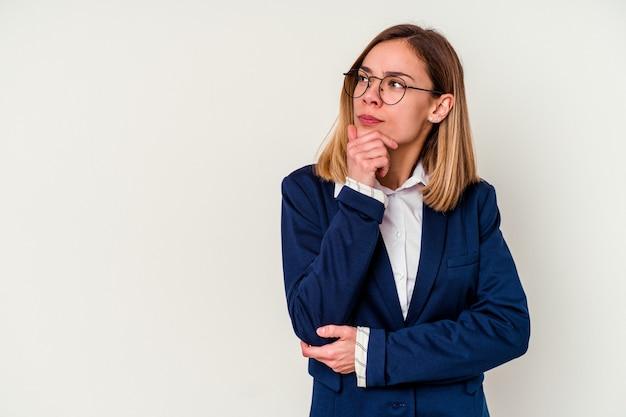 Кавказская женщина молодой бизнес изолирована на белом смотрит в сторону с сомнительным и скептическим выражением лица.