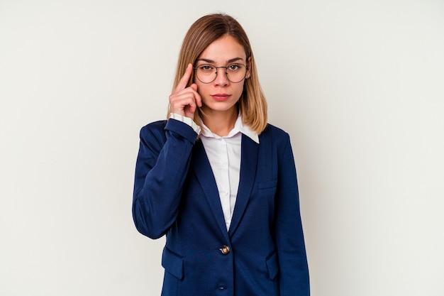 Кавказская женщина молодой бизнес, изолированные на белом указывая храм пальцем, думая, сосредоточился на задаче.