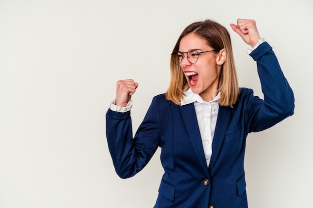 若いビジネス白人女性は、勝利、勝者の概念の後に拳を上げて白で隔離。