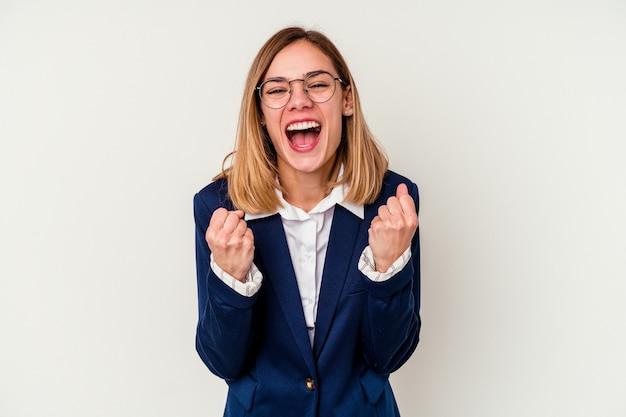 のんきと興奮して応援している白い壁に孤立した若いビジネス白人女性。利佳國際電子。